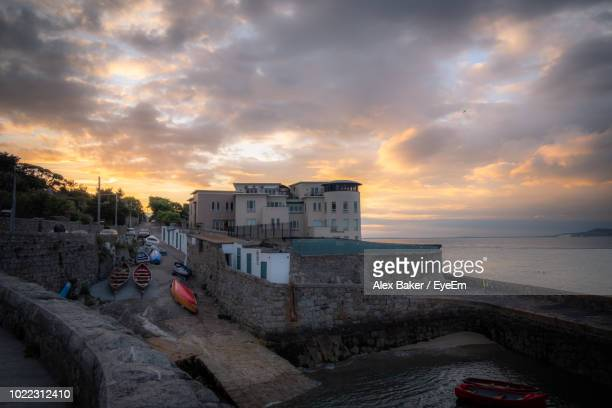 buildings by sea against sky during sunset - dalkey stock pictures, royalty-free photos & images