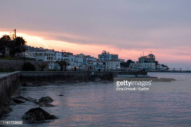 buildings by sea against sky during sunset - spetses stock pictures, royalty-free photos & images