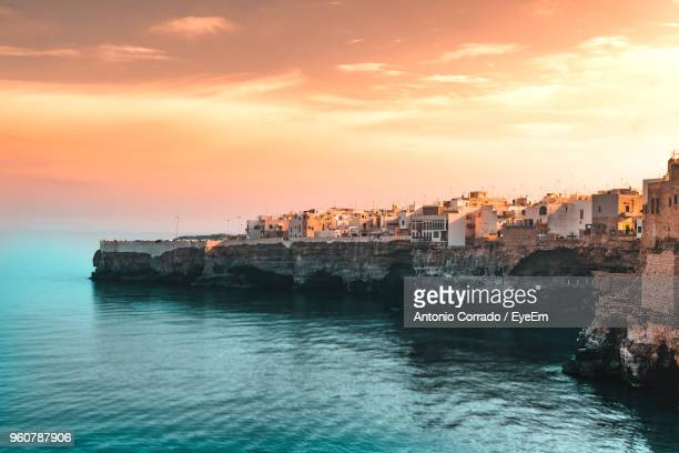 buildings by sea against sky during sunset - polignano a mare stock photos and pictures