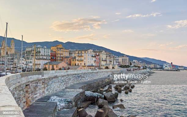 buildings by sea against sky during sunset - corsica stock photos and pictures