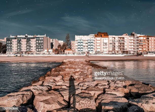 buildings by sea against sky in city and a person's shadow on the rocks - alexandra valencia stock-fotos und bilder