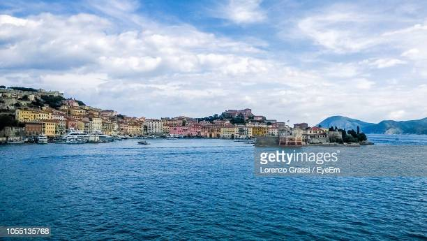 buildings by sea against sky in city - livorno stock pictures, royalty-free photos & images