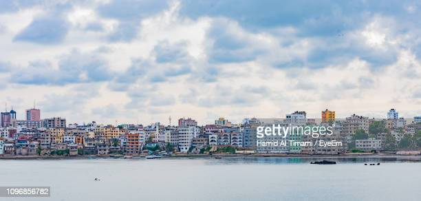 buildings by sea against sky in city - mombasa stock photos and pictures