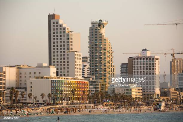 buildings by sea against sky in city - tel aviv stock pictures, royalty-free photos & images