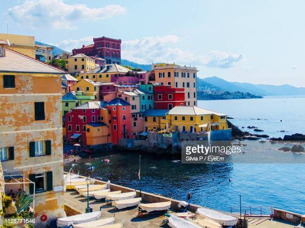 buildings by sea against sky in town - genoa stock pictures, royalty-free photos & images