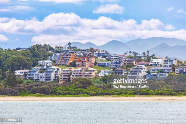 buildings by sea against sky - coffs harbour stock pictures, royalty-free photos & images