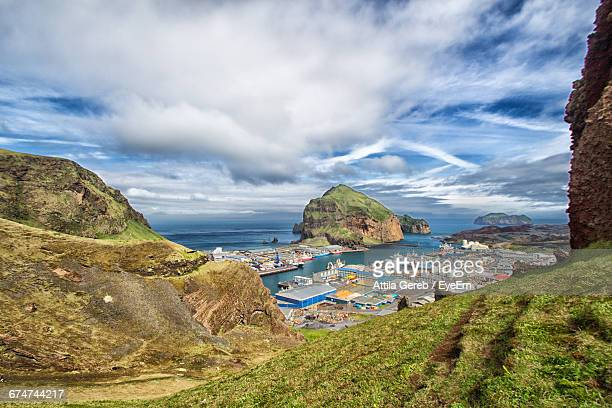 Buildings By Sea And Rock Formations Against Cloudy Sky