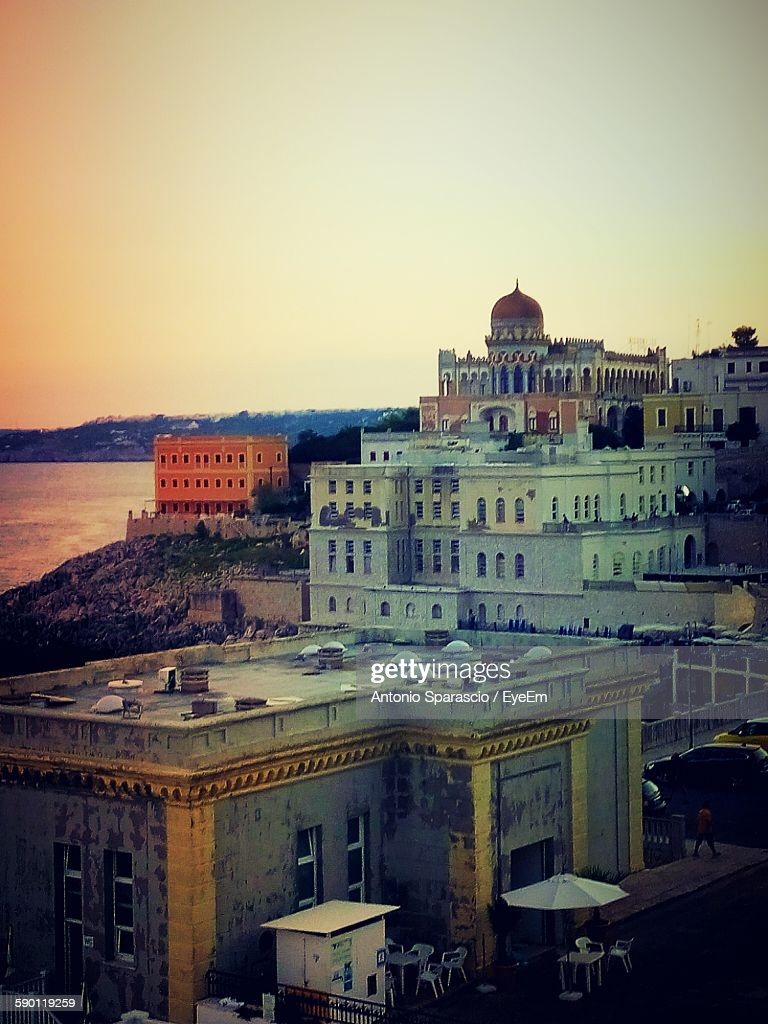 Buildings By Sea At Santa Cesarea Terme During Sunset : Stock Photo