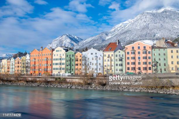 buildings by snowcapped mountains against sky - innsbruck stock pictures, royalty-free photos & images