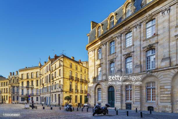 buildings by street against clear blue sky in city - bordeaux stock pictures, royalty-free photos & images