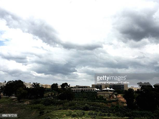 Buildings By Trees Against Cloudy Sky