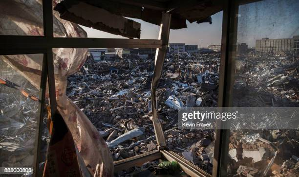 Buildings demolished by authorities are seen from a room of former dormitory for workers in an area that used to have migrant housing and factories...