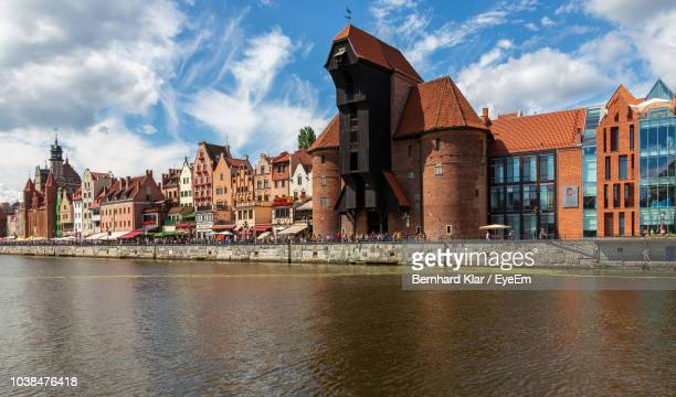 buildings in city against cloudy sky - gdansk stock pictures, royalty-free photos & images