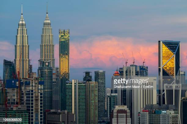 Buildings In City Against Cloudy Sky