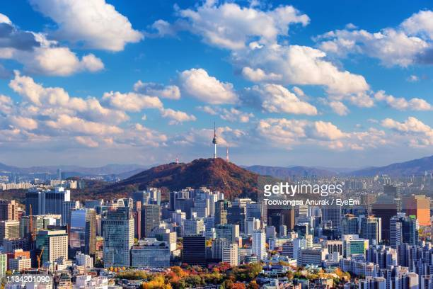 buildings in city against cloudy sky - seoul stock pictures, royalty-free photos & images