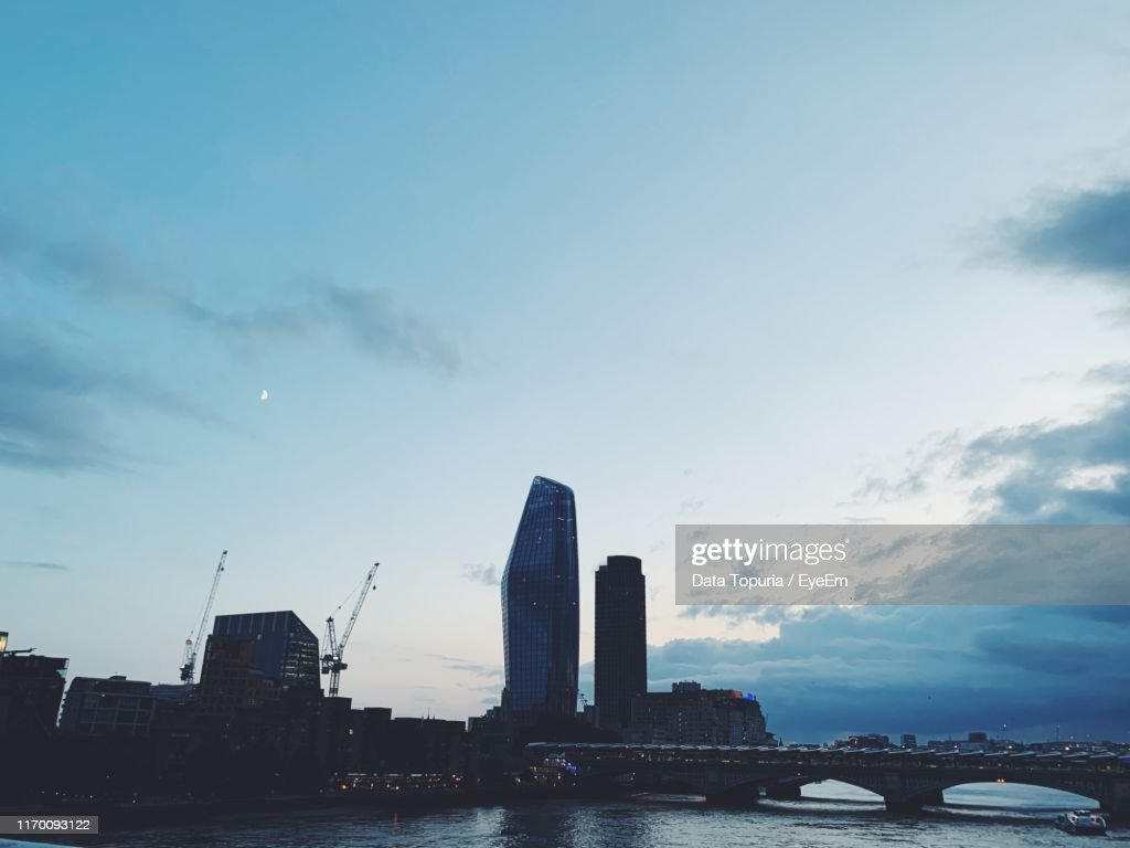 Buildings In City Against Cloudy Sky : Stock Photo