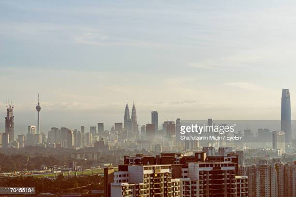 buildings in city against cloudy sky - shaifulzamri eyeem stock pictures, royalty-free photos & images