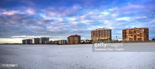 buildings in city against cloudy sky - marco island stock pictures, royalty-free photos & images