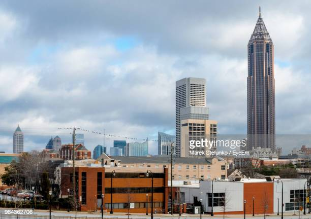 buildings in city against cloudy sky - marek stefunko stock photos and pictures