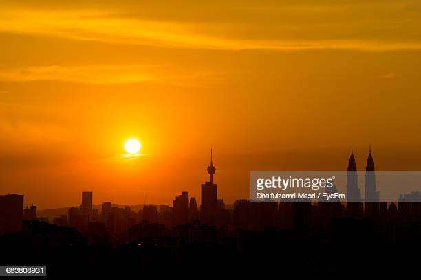buildings in city against orange sky during sunset - shaifulzamri eyeem stock pictures, royalty-free photos & images