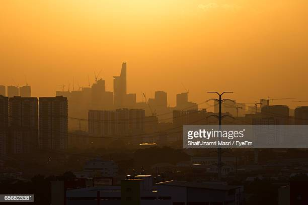 buildings in city against orange sky - shaifulzamri stock pictures, royalty-free photos & images