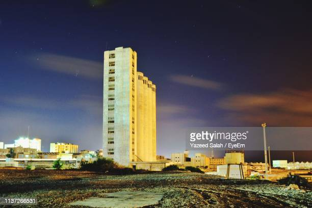 buildings in city against sky at night - salah stock photos and pictures
