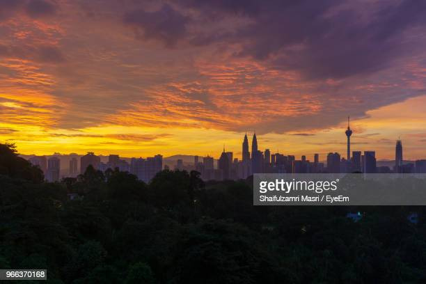 buildings in city against sky during sunset - shaifulzamri stock pictures, royalty-free photos & images