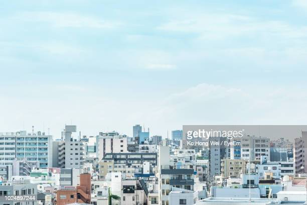 buildings in city against sky - japan stock pictures, royalty-free photos & images