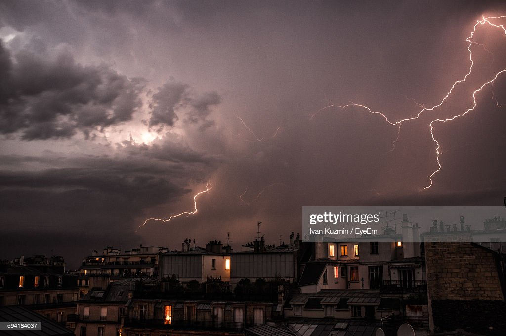 Buildings In City Against Thunderstorm At Night : Stock Photo