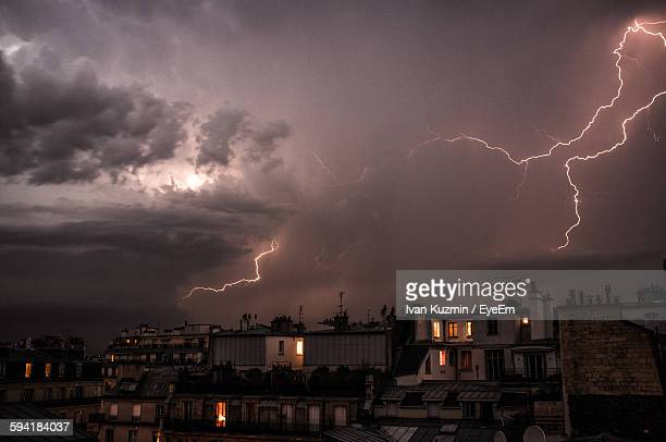 Buildings In City Against Thunderstorm At Night