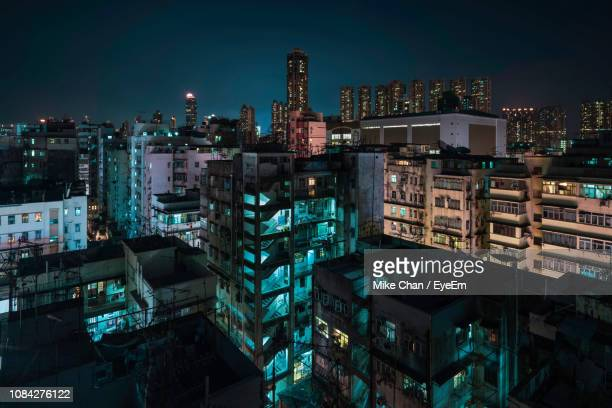buildings in city at night - kowloon stock pictures, royalty-free photos & images