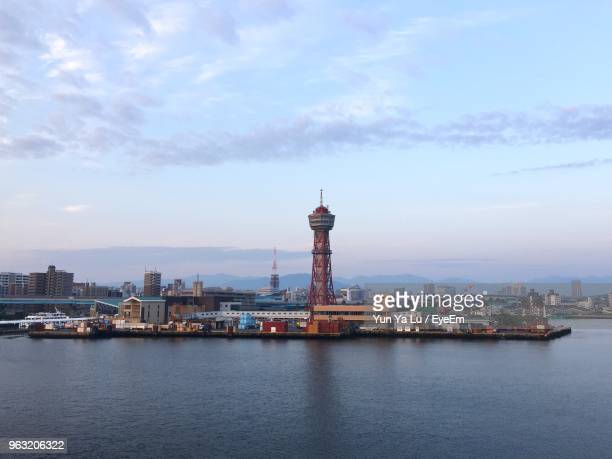 buildings in city at waterfront against cloudy sky - fukuoka city stock pictures, royalty-free photos & images