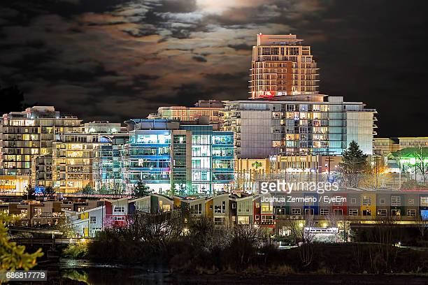buildings in city lit up at night - victoria canada stock photos and pictures