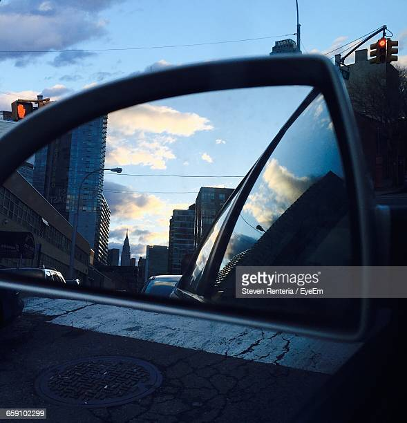 Buildings In City Reflecting On Side-View Mirror Of Car