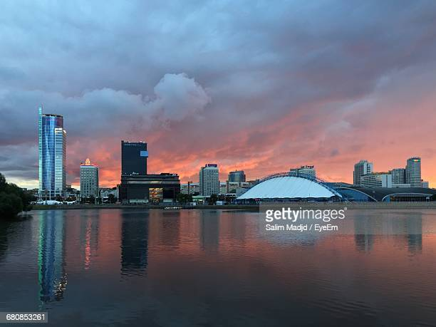 buildings in front of river against cloudy sky during sunset - minsk stock pictures, royalty-free photos & images