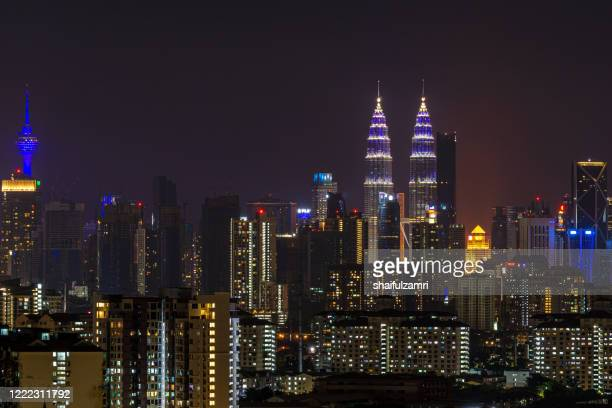 buildings in kuala lumpur illuminated in blue lights for a solidarity campaign for covid-19 front liners. - shaifulzamri stock pictures, royalty-free photos & images