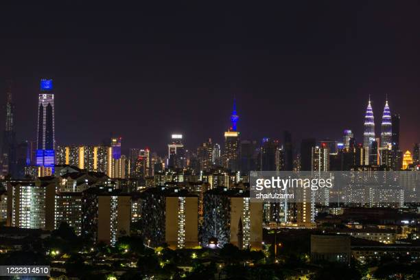 buildings in kuala lumpur illuminated in blue lights in a solidarity campaign for covid-19 front liners. - shaifulzamri stock pictures, royalty-free photos & images