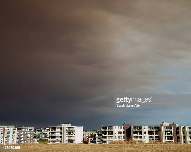 Buildings in Newington, Sydney with dry grass in the foreground and dramatic black bushfire smoke in the background
