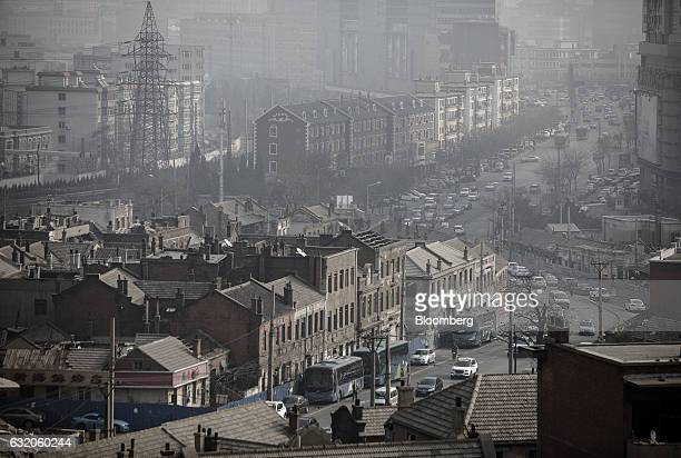 Buildings in the central business district stand beyond a neighborhood that is slated for demolition and redevelopment foreground in Dalian China on...