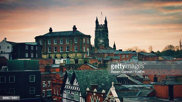 buildings in town against cloudy sky during sunrise - stockport stock-fotos und bilder