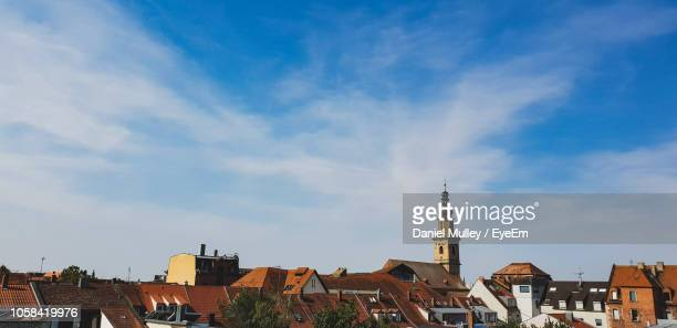 buildings in town against cloudy sky - erlangen stock photos and pictures