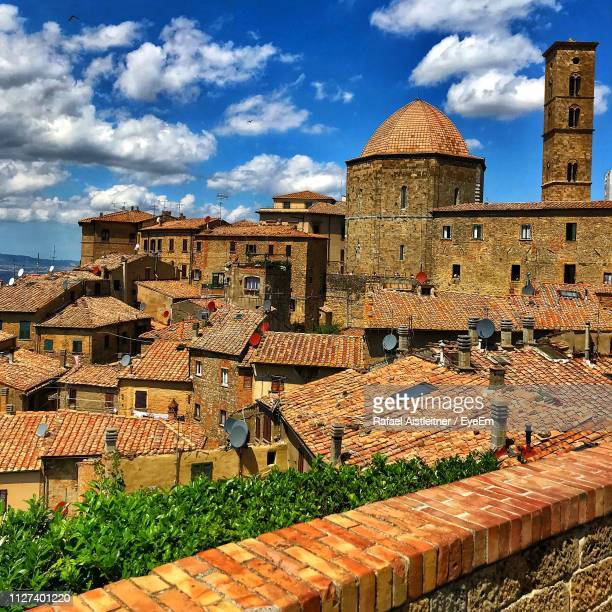buildings in town against cloudy sky - volterra stock photos and pictures
