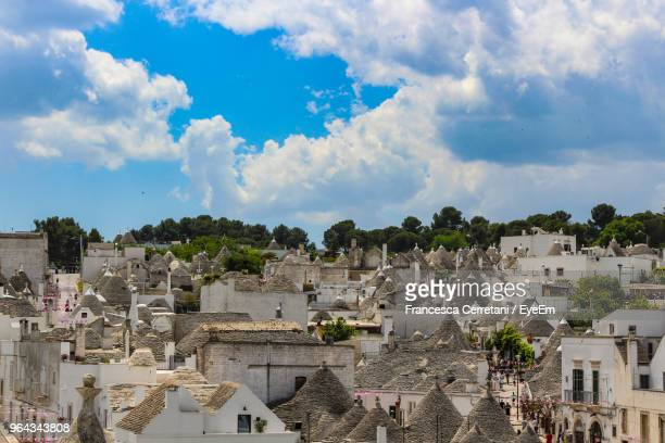 buildings in town against cloudy sky - alberobello stock pictures, royalty-free photos & images