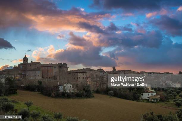 buildings in town against sky during sunset - marche italia foto e immagini stock