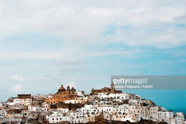 buildings in town against sky - ostuni stock photos and pictures