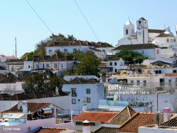 buildings in town against sky - faro district portugal stock pictures, royalty-free photos & images