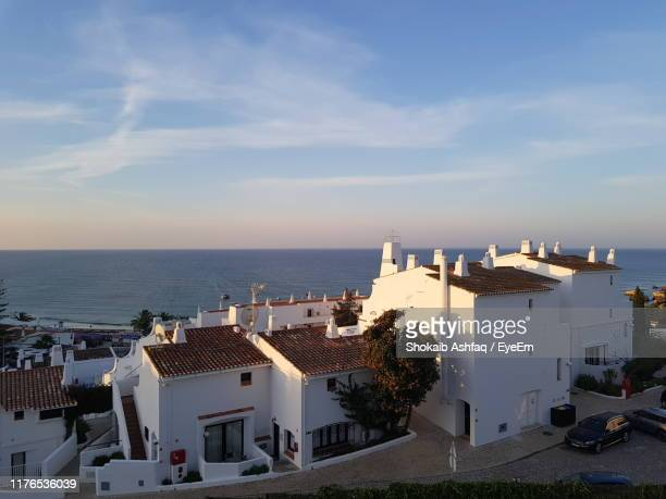 buildings in town by sea against sky - albufeira stock pictures, royalty-free photos & images