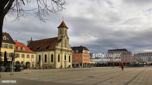 Buildings In Town Square Against Cloudy Sky