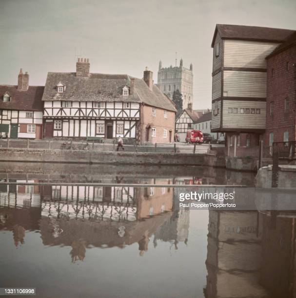 Buildings line St Mary's Road with Tewkesbury Mill on right built out over the River Avon in the market town of Tewkesbury in Gloucestershire,...
