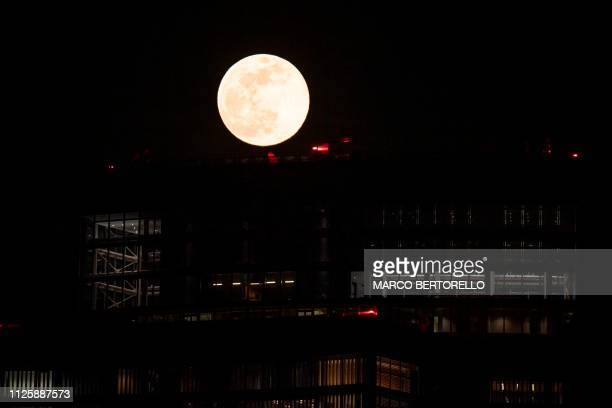 Buildings of the business district of Porta Garibaldi are pictured against the Super Snow Moon on February 19 2019 in Milan